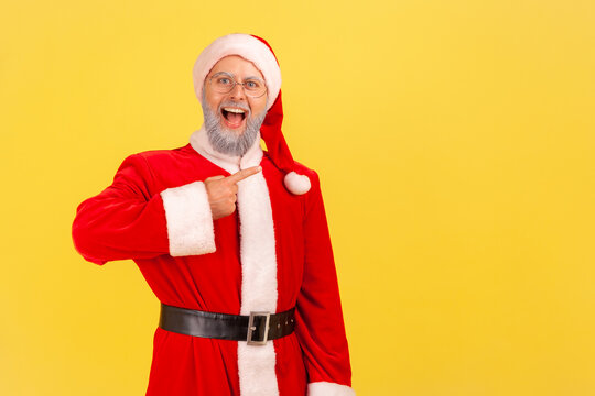 Positive excited elderly man with gray beard wearing santa claus costume with open mouth and excited expression, pointing at copy space. Indoor studio shot isolated on yellow background.