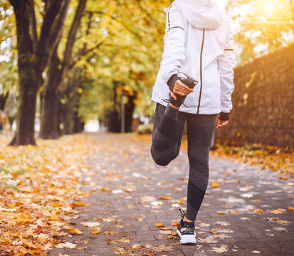Fit athletic woman doing stretching before jogging in the autumnal city park. Young fitness female runner stretching legs while warming up. Active running people concept image.
