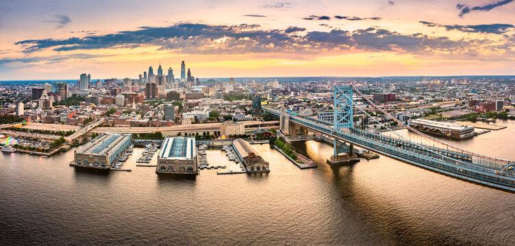 Aerial panorama with Ben Franklin Bridge and Philadelphia skyline at sunset. Ben Franklin Bridge is a suspension bridge connecting Philadelphia and Camden, NJ.