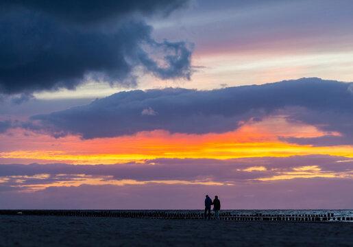 Paar geht nach dem Sonnenuntergang bei einem farbigen Gewitterhimmel am Strand der Ostsee spazieren