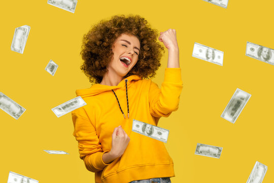 Money rain. young woman celebrating richness and enjoying.