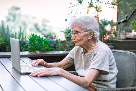 old woman using laptop on terrace
