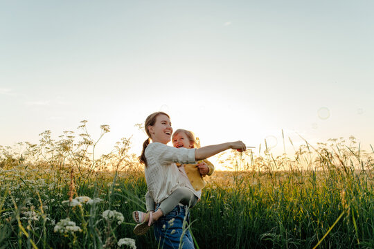Mother and daughter blowing bubbles in meadow