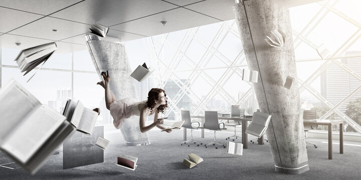 Young woman levitates while reading a book