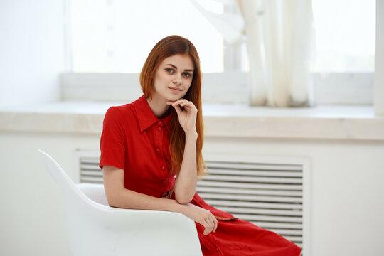 beautiful woman in red dress sitting near the window elegant style