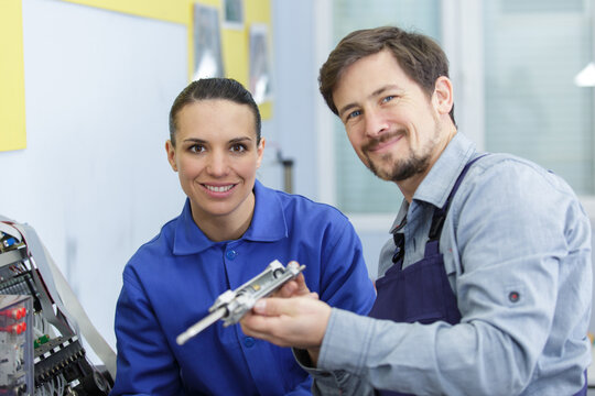 engineer working with apprentice holding machinery part