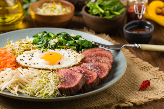 Korean beef with sprouts, spinach and fried egg.