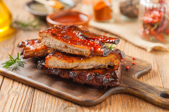 Roasted pork ribs in a bbq sauce. Served on a wooden board. Front view.