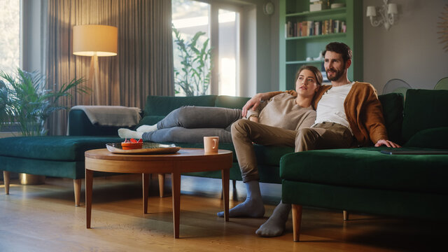 Couple Watches TV while Sitting on a Couch in the Living Room. Girlfriend and Boyfriend Lying Embracing. Spending Weekend Together at Home with Stylish Interior.