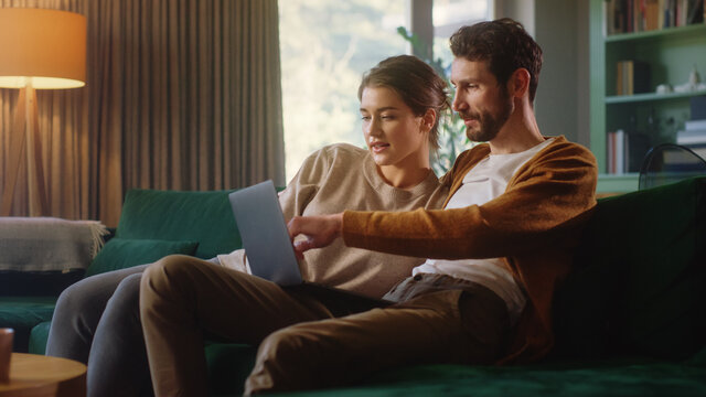 Young Couple Use Laptop Computer, while Sitting on a Couch in the Cozy Stylish Apartment. Boyfriend and Girlfriend Shopping on Internet, Watching Videos and Streaming Service.