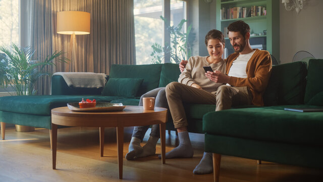 Couple Use Smartphone Device, while Sitting on a Couch in the Cozy Apartment. Boyfriend and Girlfriend Talk, do e-Shopping on Internet, Watching Funny Videos, Use Social Media, Streaming Service.