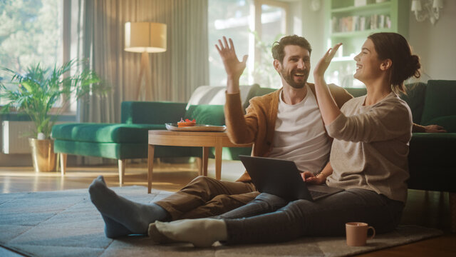 Couple Use Laptop Computer, Do and Miss High-Five in Celebration, while Sitting on the Living Floor room of their Apartment. Boyfriend and Girlfriend Talk, Have Fun, Joke, Smile, Laugh