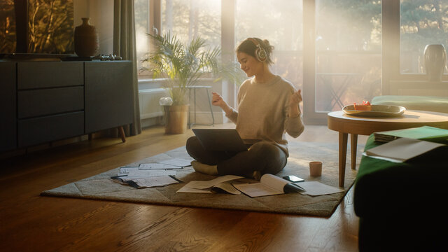 Young Woman Using Laptop at Home, Does Remote Work, Listens Music through Headphones, Brainstorms Creative Project Research. Beautiful Smiling Girl Sitting on the Floor, Enjoy Music, Dances a Bit