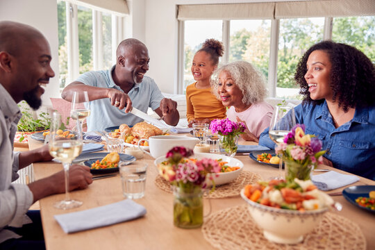 Grandfather Carving As Multi Generation Family Sit Around Table At Home And Enjoy Eating Meal