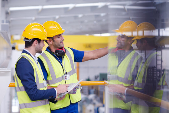 Supervisor and worker talking in steel factory