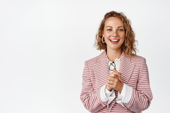 Young businesswoman clench hands, looking with hopeful face expression, smiling and looking at camera with anticipation, standing against white background