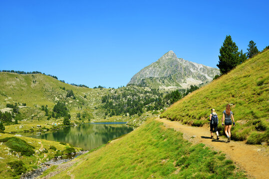 Hikers on a trip in Neouvielle national nature reserve, Lac du Milieu, French Pyrenees. Beautiful summer mountain landscape in the sunny day.