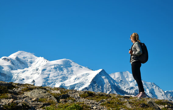 Hiker looking at the Mont Blanc from the summit of Le Brevent. French Alps, Chamonix, France.