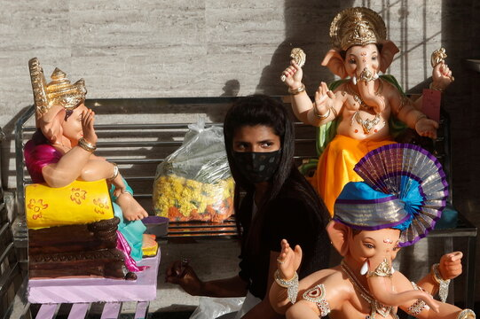 An artist wearing protective mask gives finishing touches to an idol of Hindu God Ganesh on the eve of the Ganesh Chaturthi festival in Mumbai
