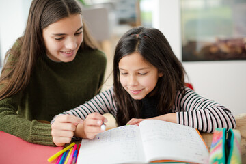 Girl helping young sister with homework
