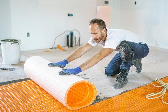 Man worker install orange roll membrane waterproofing on the floor