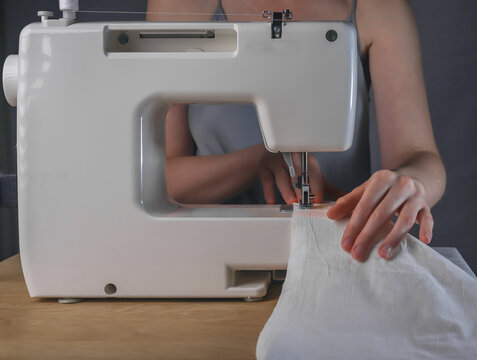 Seamstress hands with linen cloth at sewing machine, working process with organic natural cotton textile.