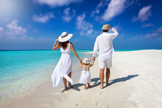 A elegant family in white summer clothing walks hand in hand down a tropical paradise beach and enjoys their holidays
