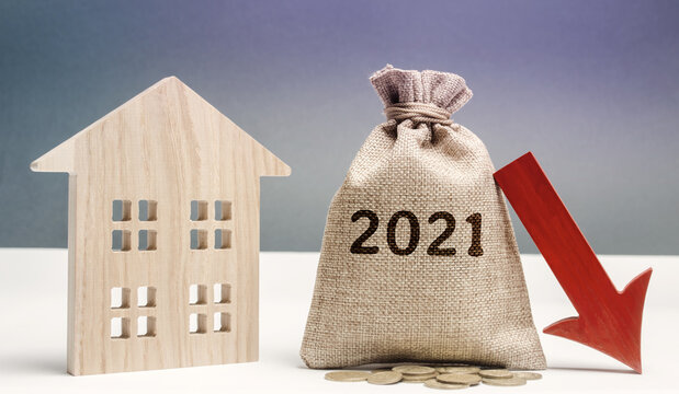 Wooden house and 2021 money bag with down arrow. Forecasting the real estate market concept. Interest rates falling. Investment, profit and income. Decline in housing prices. Mortgage, loan.