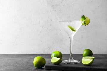 Fototapeta Glass of tasty margarita cocktail and limes on light background obraz