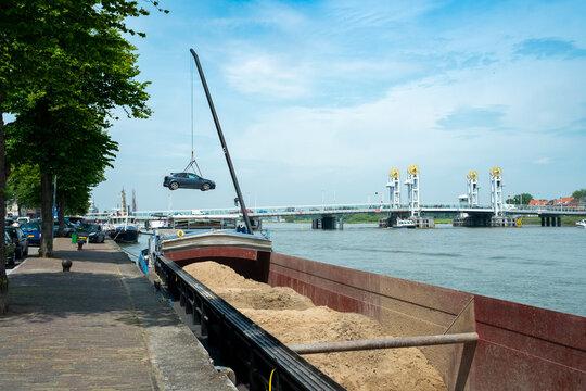 A skipper puts his car ashore with a crane at the city bridge in Kampen, Overijssel Province, The Netherlands