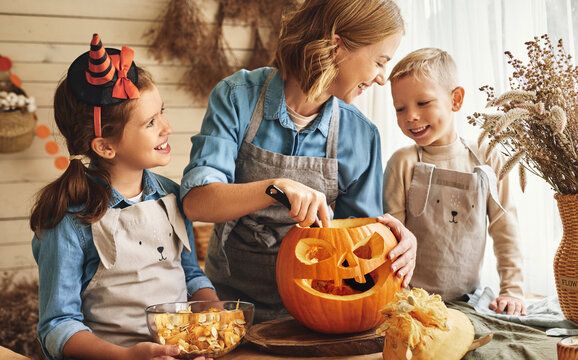 Happy family mother and kids carving pumpkin for Halloween holiday together at home