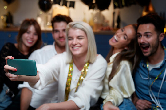 Cheerful friends taking selfie on the party