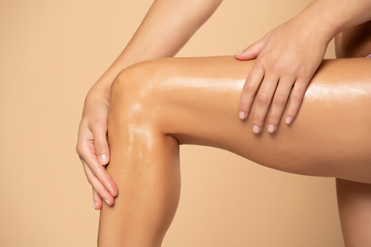 Close-up on a woman applying cream on her legs