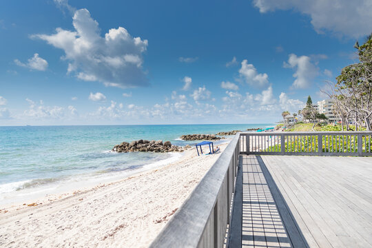 Landscape photograph of a large deck with railing overlooking the Atlantic Ocean at Deerfield Beach Florida under a cloudy blue sky.