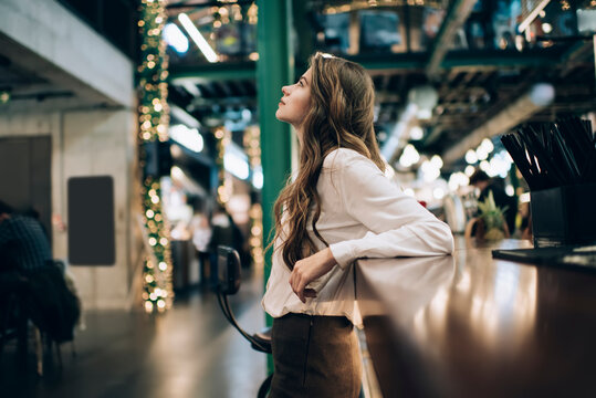 Young female customer in white shirt thinking about restaurant business standing near bar indoors, contemplative hipster girl with curly brunette hair pondering on idea for spending leisure weekend