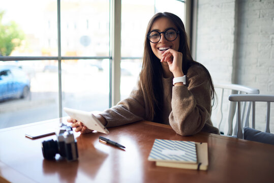 Portrait of cheerful hipster girl in stylish spectacles for vision protection smiling at camera during free time in cafe interior, happy Middle Eastern female blogger with touch pad technology