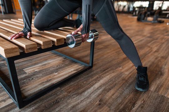 Fitness woman working and trains with dumbbells in the gym