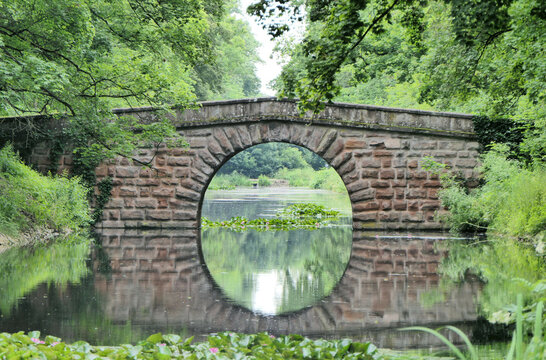 Stone bridge over a river, which is reflected in the water and forms a circle.