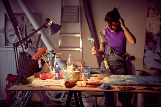 A young female artist in a creative process of making a new painting in the studio. Art, painting, studio