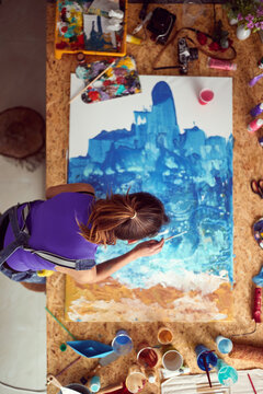 A bird's-eye view of a young female artist who is working on the painting in her studio. Art, painting, studio