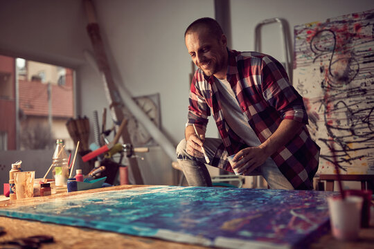 A young male artist in the studio is having a good time while working on his new painting. Art, painting, studio