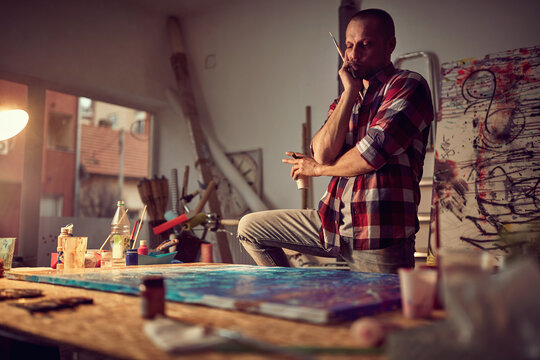 A young male artist in a creative process while working on his new painting in the studio. Art, painting, studio