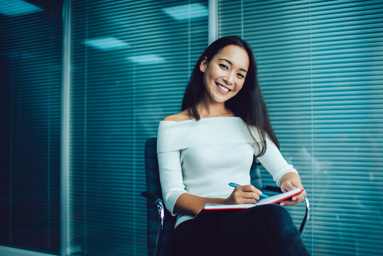 Portrait of Asian female employee with textbook creating business management and organization plan, cheerful professional woman enjoying own occupation holding notepad and smiling at camera