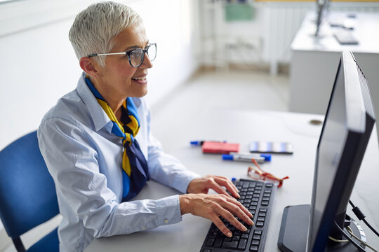 A female professor in front of a computer desk at the informatics lecture. Professor working at the college. Education, college, university, learning and people concept