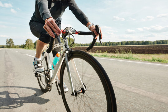 Close-up of cyclist in sports clothing riding a bike on a country road