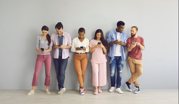 Indoor shot of diverse international group of happy young millennial people leaning on wall, looking at screens of mobile phones, connecting to free wi fi, using messengers, watching online streams