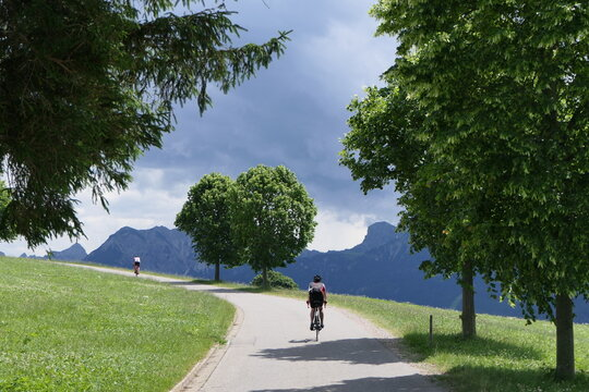 Ascent on the day by two cyclists with a magnificent mountain backdrop in the Alps.