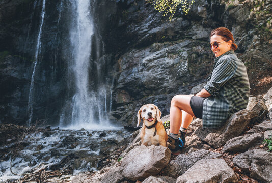 Smiling Female dog owner and his friend beagle dog resting near the mountain river waterfall during their together walking in autumn season time. Human and pets or walking in nature concept image.