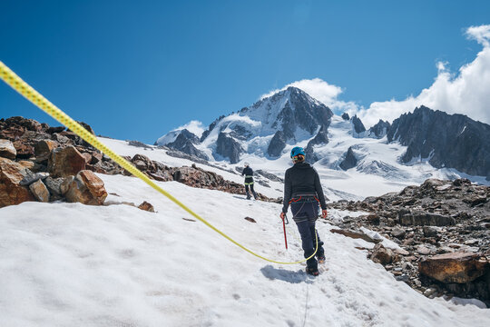 Two females Rope team members on acclimatization day dressed in mountaineering clothes walking in crampons with ice axes by snowy slopes in a climbing harness and dynamic rope on close-up foreground