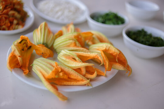 Zucchini flowers or courgette flowers on a white plate background. over white wooden table.  Organic food.